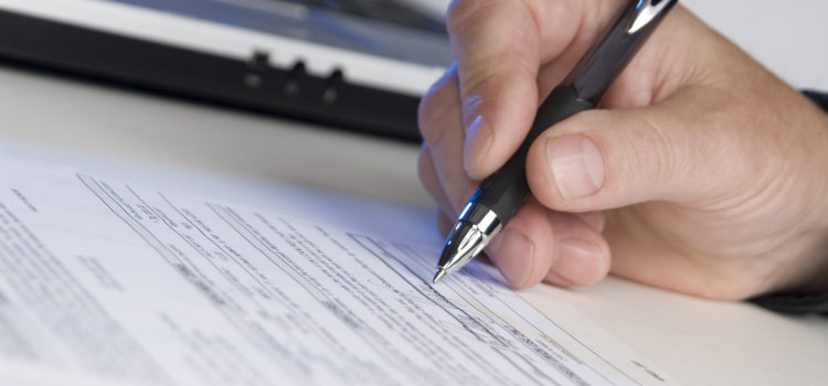 man's hand holding a pen writing a signature, computer in background