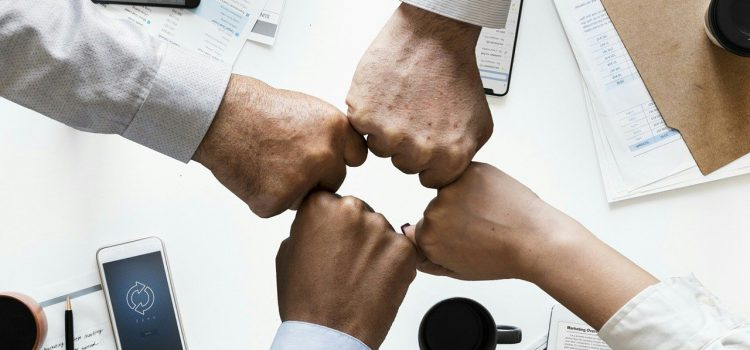 Quattro pugni uno vicino all'alto per simboleggiare che insieme si può raggiungere il successo aziendale.